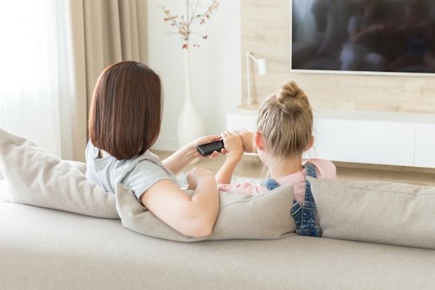 Mutter und tochter, die auf dem sofa fernsieht, kämpfend für fernbedienung sitzen