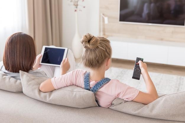 Mutter und tochter, die auf der couch fernsieht im wohnzimmer sitzen
