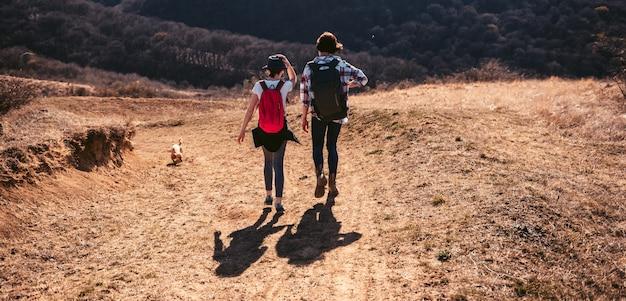 Mutter und tochter, die auf gebirgspfad wandern