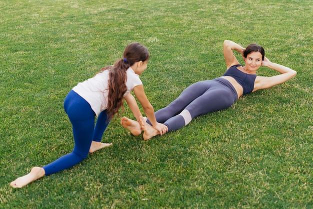 Mutter und tochter, die auf grünem gras trainieren