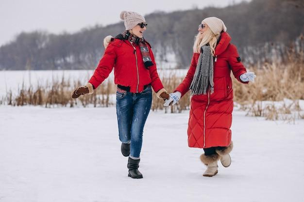Mutter und tochter, die auf see in der winterzeit laufen