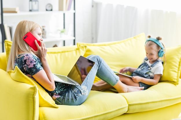 Mutter und tochter, die auf sofa unter verwendung des elektronikgeräts sitzen