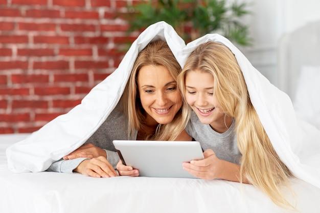 Mutter und tochter, die auf tablette schauen