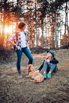 Mutter und tochter, die beim hund im wald während des sonnenuntergangs liegen