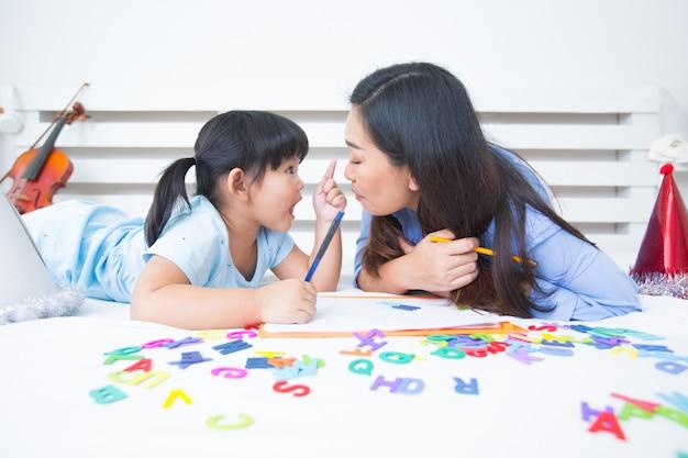 Mutter und tochter, die das alphabet studieren