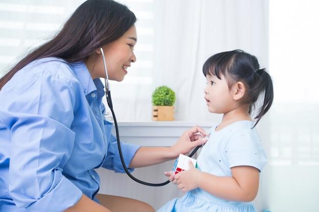 Mutter und tochter, die doktor mit stethoskop spielen