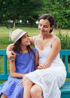 Mutter und tochter, die draußen auf bank umarmen