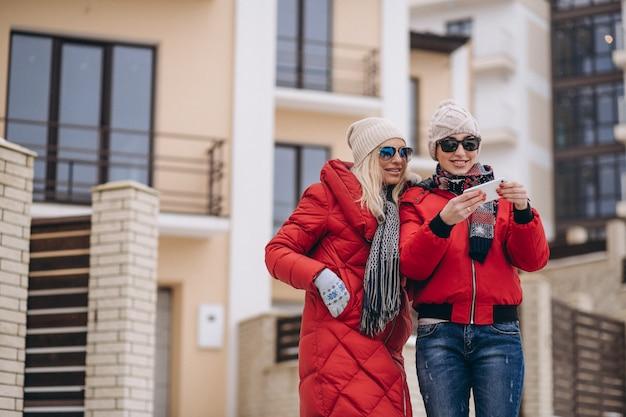 Mutter und tochter, die draußen selfie im winter tun