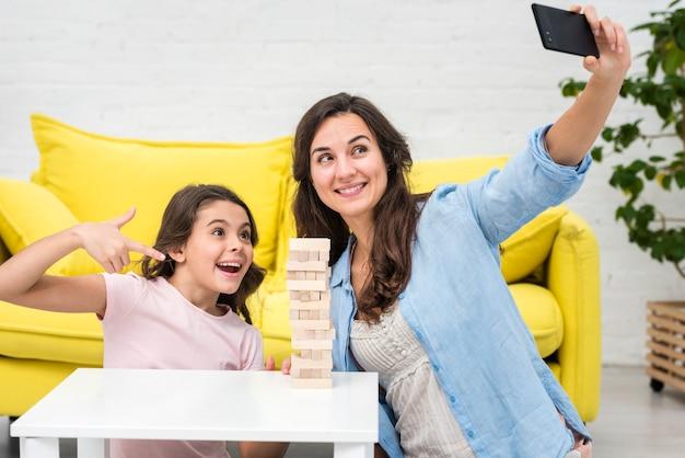 Mutter und tochter, die ein selfie beim spielen eines hölzernen turmspiels nehmen