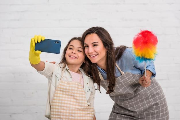 Mutter und tochter, die ein selfie mit reinigungsgegenständen nehmen