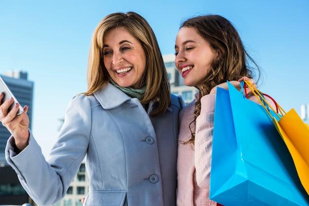 Mutter und tochter, die ein telefon betrachtend lächeln