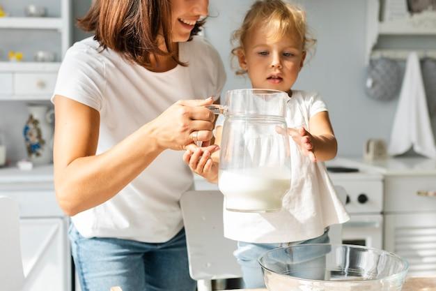 Mutter und tochter, die eine tasse milch halten