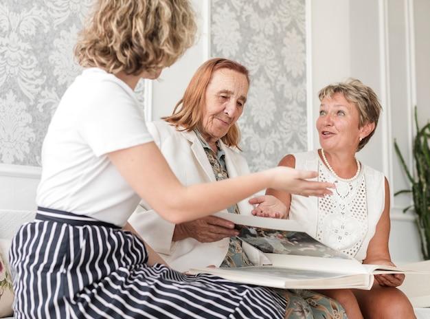 Mutter und tochter, die etwas beim schauen des fotoalbums sprechen