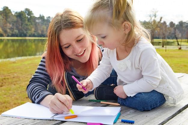 Mutter und tochter, die farben in einem park zeichnen