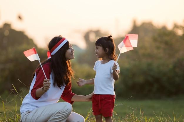 Mutter und tochter, die flagge von indonesien hissen