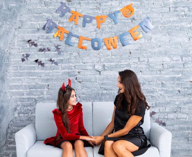Mutter und tochter, die für halloween aufwerfen