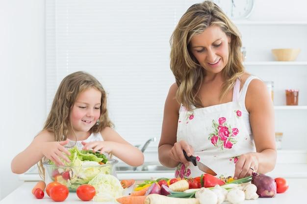Mutter und tochter, die gemüse vorbereiten