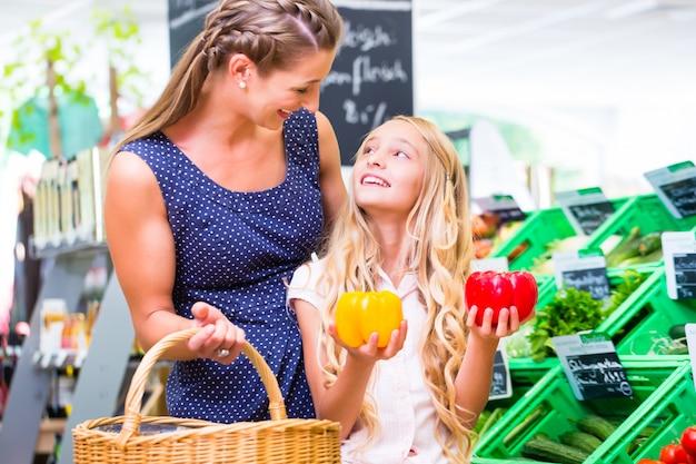 Mutter und tochter, die gemüse während einkauf im organischen supermarkt auswählen