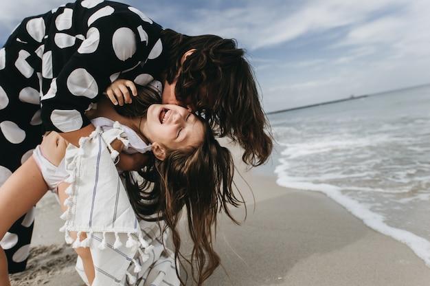 Mutter und tochter, die hände halten und auf strand gehen