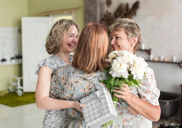 Mutter und tochter, die ihre großmutter mit geschenk- und blumenblumenstrauß zu hause halten umarmen