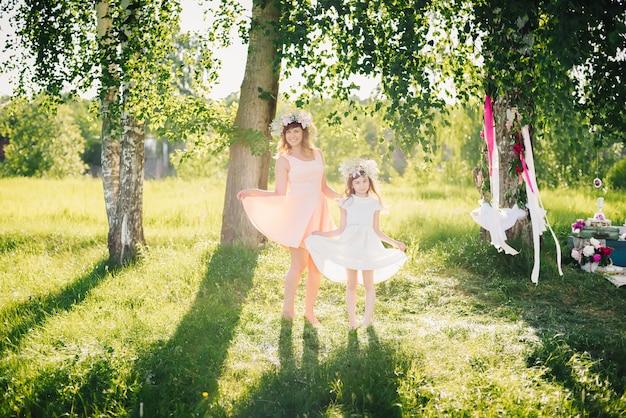 Mutter und tochter, die im park auf einem sonnigen sommer aufwerfen