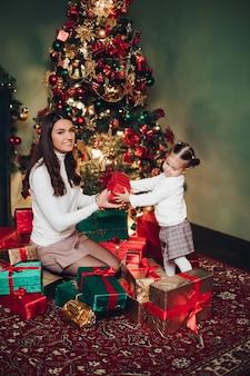 Mutter und tochter, die im stapel von geschenken umarmen.