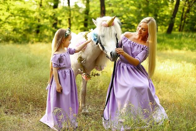 Mutter und tochter, die im wald mit einem weißen pony sitzen.