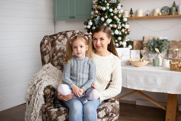 Mutter und tochter, die im weihnachtshintergrund sitzen