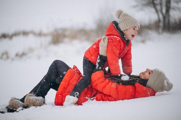 Mutter und tochter, die im winterpark spielen