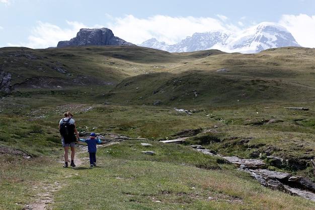 Mutter und tochter, die in den alpinen bergen nahe sunnega in der schweiz wandern.
