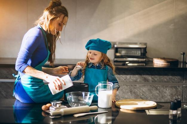Mutter und tochter, die in der küche backen