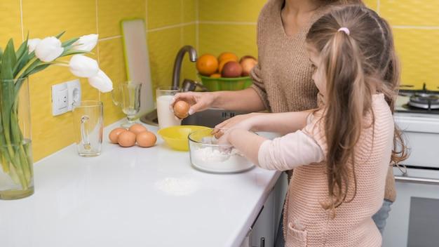 Mutter und tochter, die in der küche kochen