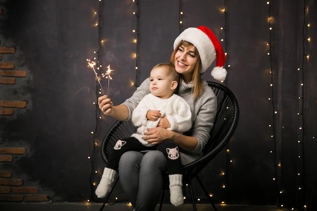 Mutter und tochter, die in einem stuhl auf weihnachten sitzen