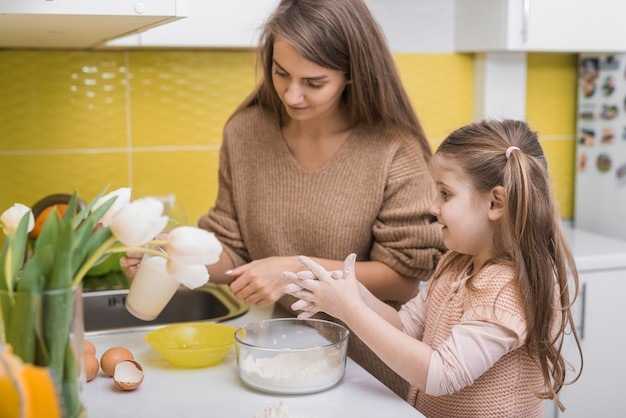 Mutter und tochter, die lebensmittel in der küche kochen