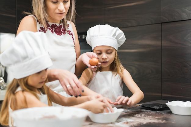 Mutter und tochter, die lebensmittel in der küche zubereiten