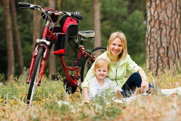 Mutter und tochter, die nahe bei fahrrad sich entspannen