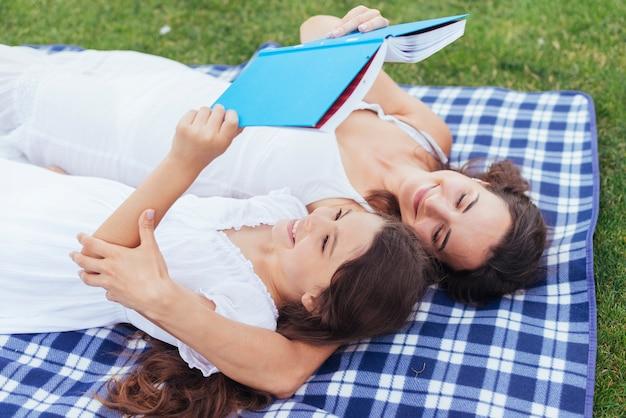 Mutter und tochter, die niederlegen und lesen