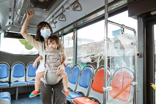 Mutter und tochter, die öffentliche verkehrsmittel während der pandemie tragen gesichtsmaske reiten