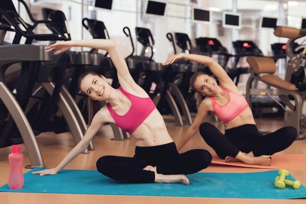 Mutter und tochter, die pilates übungen an der turnhalle tun