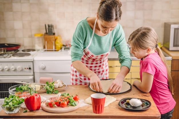 Mutter und tochter, die pizza zubereiten