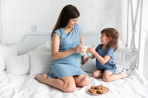 Mutter und tochter, die schokoladenplätzchen und trinkmilch essen