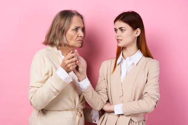 Mutter und tochter, die sich an den händen fürsorgliche familie halten, lieben rosa hintergrund