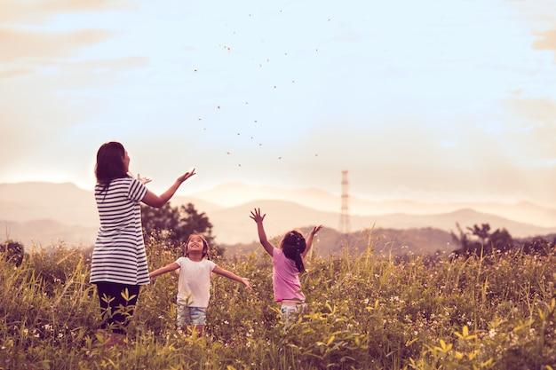 Mutter und tochter, die spaß haben und zusammen im getreidefeld spielen