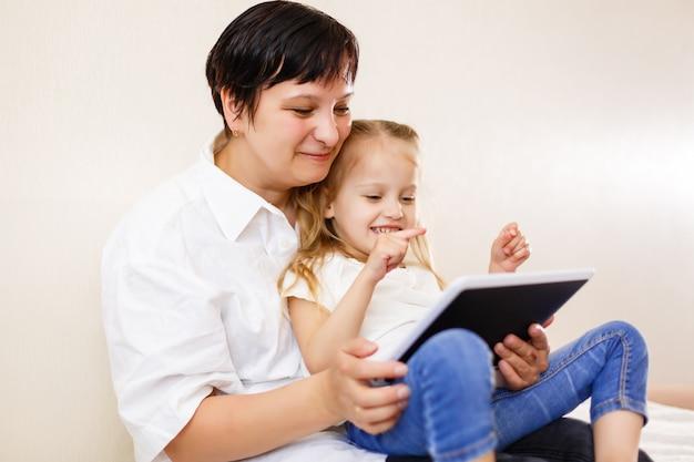 Mutter und tochter, die tablette verwendet mutter und tochter, die zusammen tablet-computer verwendet