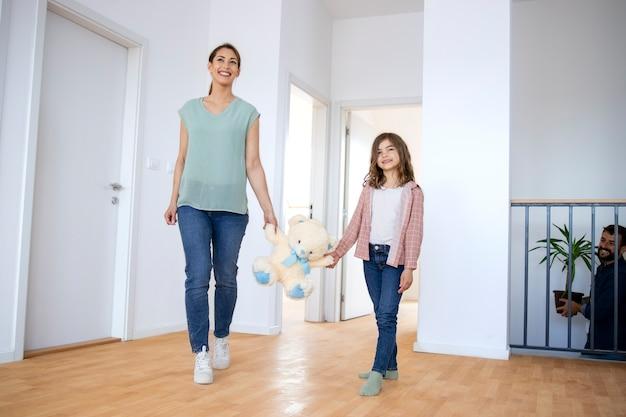 Mutter und tochter, die teddybärspielzeug halten und ihr neues haus betreten.