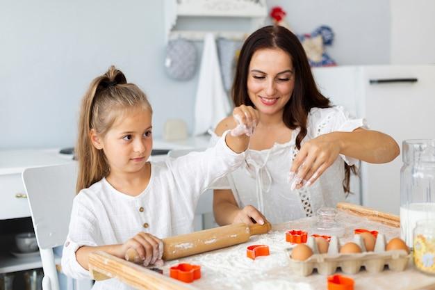 Mutter und tochter, die teig für plätzchen zubereiten