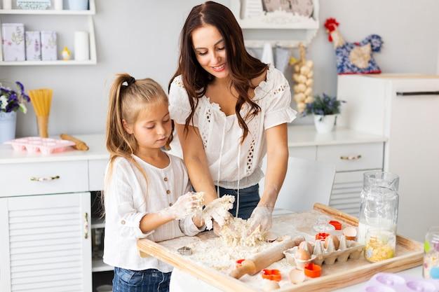 Mutter und tochter, die teig zubereiten