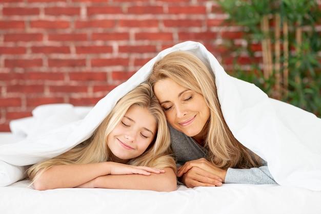 Mutter und tochter, die unter blatt stillstehen