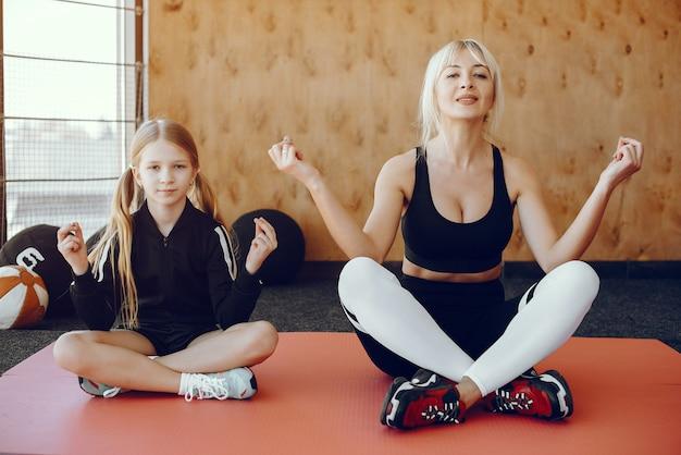 Mutter und tochter, die yoga in einem yogastudio tun