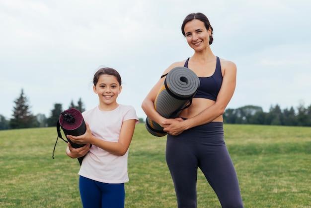 Mutter und tochter, die yogamatten halten